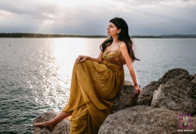 Austin woman poses for a Lifestyle Portrait Session sitting on rocks by the lake