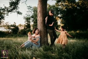 Texas Family posing for a Lifestyle portrait under a big tree with a Joyful High-five