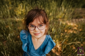 Rhone little girl with blue eyes poses for a Lifestyle Portrait Session in the tall grass