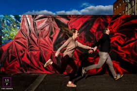 Perpignan couple running for a creative Lifestyle image along an urban Love street