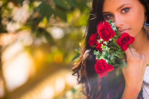 Minas Gerais lifestyle teen portrait session with a young woman holding a bouquet of flowers by her face, in Brazil