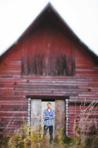 Seattle teen lifestyle portrait of a young man standing before a red barn on the farm