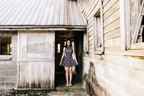 Seattle WA teen lifestyle portrait of a girl holding out her dress in a rural farm building