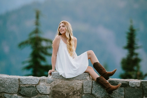 Seattle Washington teen lifestyle portrait of a girl on a stone wall in the mountains in a dress with cowboy boots