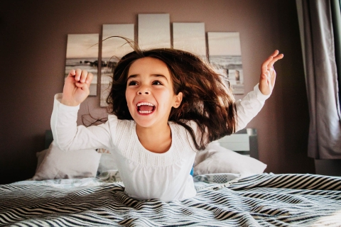 France Creative Lifestyle Portrait image of The little girl who jumps on the bed at home