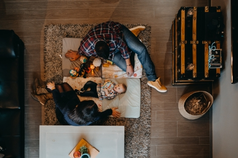 Pyrenees-Atlantiques Lifestyle Photographer created this artistic portrait showing the view from the mezzanine of the living room on the parents playing with their baby