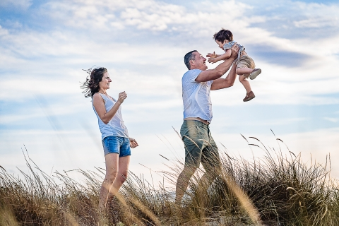Perpignan Family posing for a Lifestyle portrait In the wind in the tall blowing grasses
