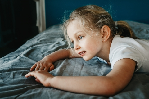 Perpignan young girl poses for a Lifestyle Portrait Session with a six-year old daydreaming on her parents' bed in France