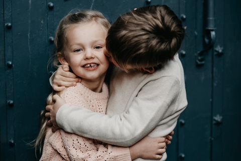 Barcelona siblings posing for a Lifestyle portrait as Brother is kissing his little sister in Spain