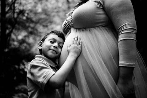 Knoxville Mother and young son posing for a Lifestyle Maternity Portrait while Showing baby sister some love