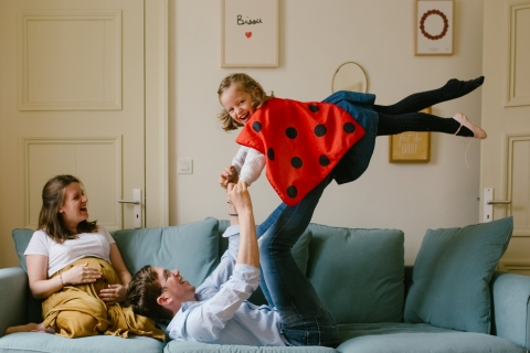 Doubs Family posing for a Lifestyle portrait while doing ladybug superman with daddy