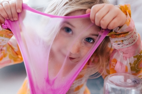 London young girl poses for a Lifestyle Portrait Session as she is Looking through the slime