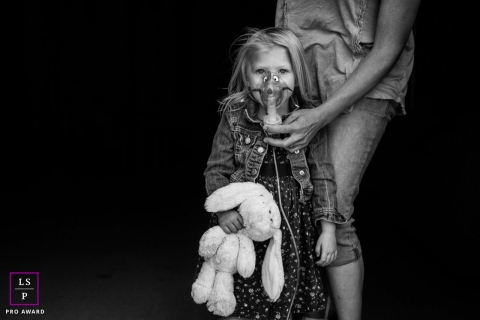 Lifestyle Family Portrait Session in Arizona United States | Photo contains: girl, mother, stuffed animal, black, white, oxygen mask