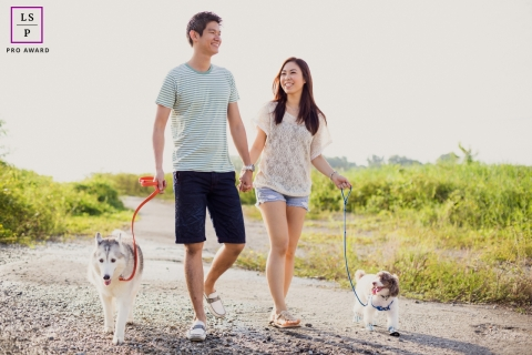 Lifestyle Couple Portrait Photography in | Image contains: dogs, man, woman, dirt road, smiling, walking, sky, ouside