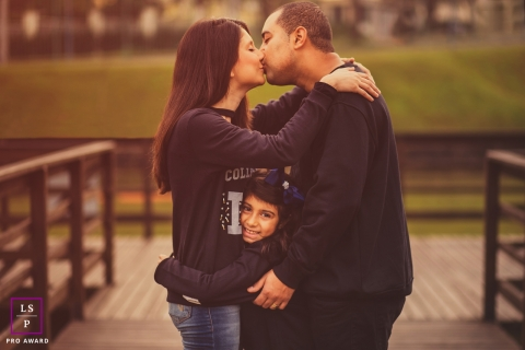 Lifestyle Family Portrait Photography in Rio Grande do Sul Brazil | Image contains: father, mother, kissing, hugging, girl, outside
