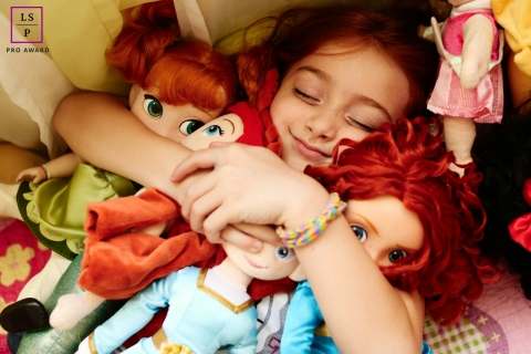 Lifestyle Family Portrait Photography in Rio de Janeiro Brazil | Image contains: girl, hugging, dolls, close-up, indoors, smile