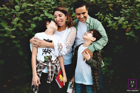 Lifestyle Family Portrait Photography in Rio Grande do Sul Brazil | Image contains: family, boys, mother, father, bushes, color, outside, hugging