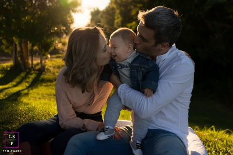 Lifestyle Family Portrait Photography in London England | Image contains:sunset, mother, father, baby, color, trees, kissing