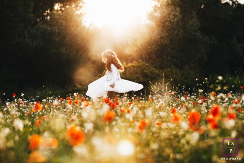 Family Photographer in Barcelona Spain | Lifestyle Image contains: girl, portrait, field, flowers, sunlight, outdoors, dress, spin