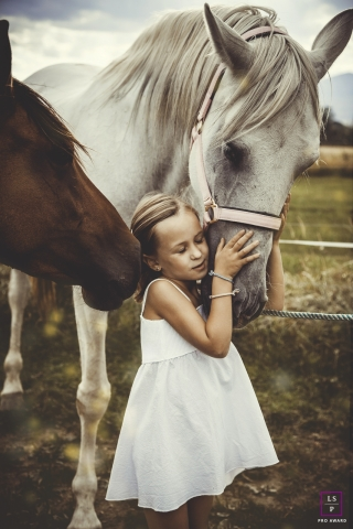 Girl Portraits in Barcelona Spain | Lifestyle Photography Session contains: child, horses, hug, outdoor