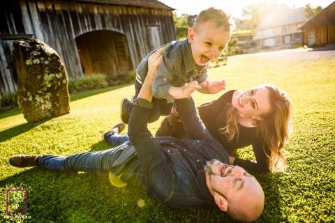 Rio Grande do Sul Family Lifestyle Portrait Session Brazil | Photo contains: home, barn, grass, mom, dad, son, play, lift