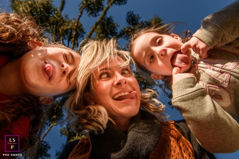 Rio Grande do Sul Family Lifestyle Portraits Brazil - Photo contains: mom, daughters, silly, faces, tongues, close-up, trees