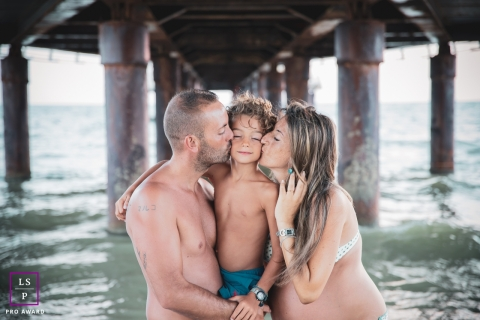 Pistoia Family and Maternity Lifestyle Portrait Session Tuscany | Photo contains: mom, dad, son, sea, water, waves, pier, love