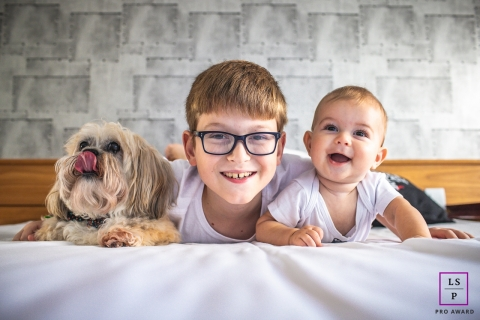 Sao Paulo Lifestyle Family Portrait Session with the Kids and Dog | Photo contains: boy, baby, dog, indoors, wall, color, bed, tongue, smile