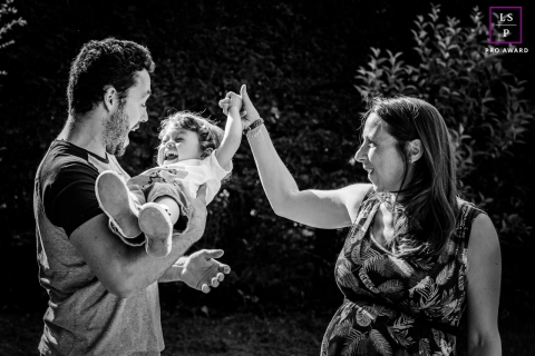 Occitanie Lifestyle Family Portraits in Haute-Garonne | Image contains: mom, dad, toddler, child, park, trees, sun, black and white