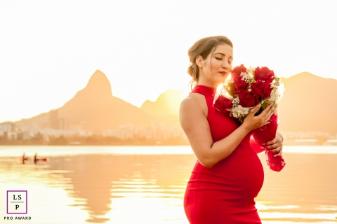 Rio de Janeiro Brazil Maternity Portrait Photography | Lifestyle session with flowers at the water in a red dress