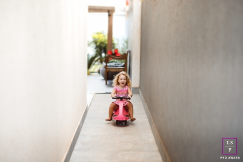 Young Girl Portraits in Federal District | Lifestyle Photography Session contains: toys, patio, yard, bike, push, ride, riding