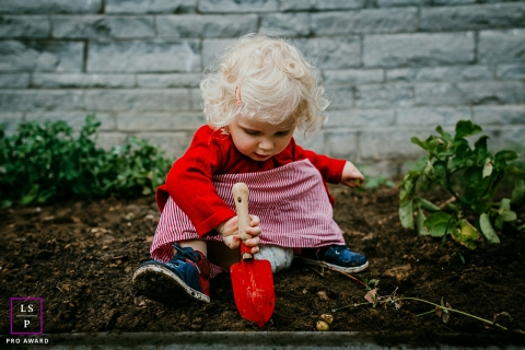 Toddler Girl Portraits in Brabant Wallon | Lifestyle Photography Session contains: garden, shovel, red, toddler, girl