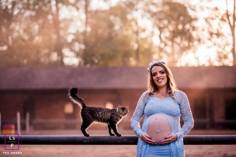 Maternity Photographer in Rio Grande do Sul Brazil | Lifestyle Image contains: dress, flowers in hair, cat, kitty, rail, rural