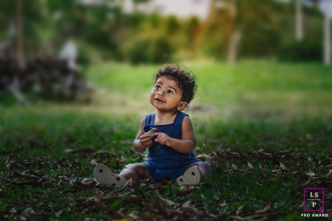 Minas Gerais Lifestyle photo shoot of a young toddler child sitting on the grass.