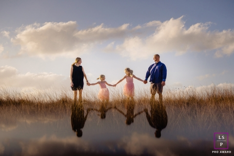 Key West	Florida Family reflections - Lifestyle portraits in grass with clouds overhead.