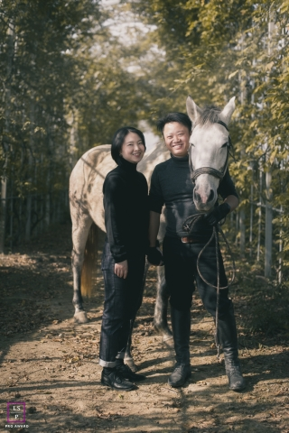 Hunan China couple portrait dressed in all black. Lifestyle session with a white horse.