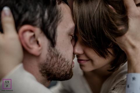 Maine-et-Loire close-up engagement portrait of a couple holding each other closely.