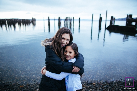 Seattle girls hugging next to water during a family portrait session