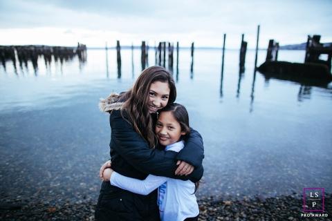 Meninas de Seattle, abraçando-se ao lado da água durante uma sessão de retrato de família