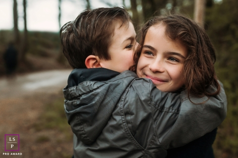 A brother holds his sister tightly for this family portrait in France