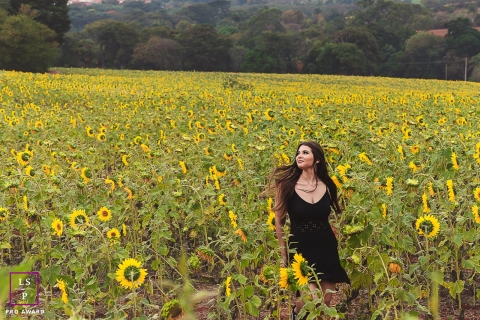 A young woman walking through a field of sunflowers during a lifestyle portrait session