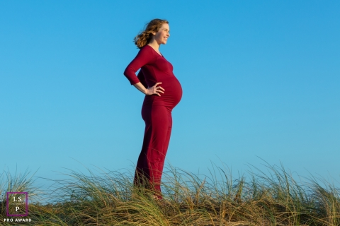 California woman stands as a superhero as she has a portrait taken for her maternity session
