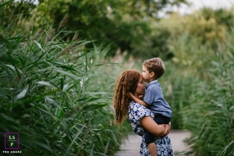 A young boy hugs and kisses his mother during this France Lifestyle Portrait Session