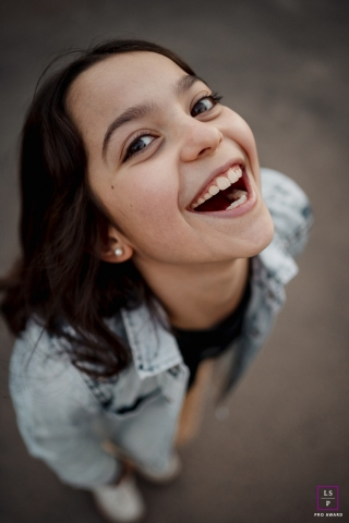 A lifestyle teen portrait with a big smile, shot overhead
