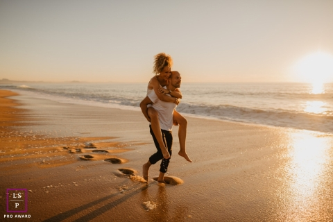 A France lifestyle couple portrait shoot in New Aquitaine showing him Lifting up his girlfriend on the beach during engagement session