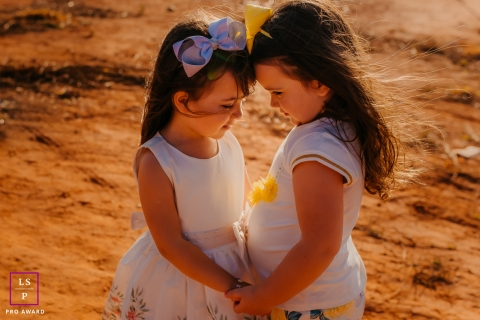Minas Gerais lifestyle kids portrait session with two young girls with bows in their hair in Brazil