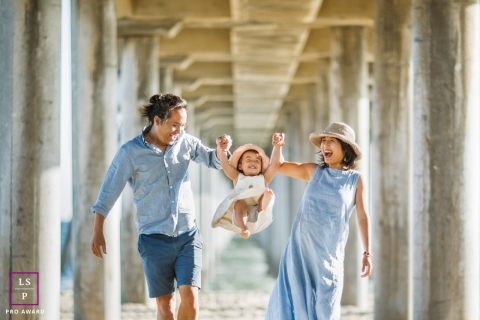 A San Francisco California lifestyle family portrait session with a couple swinging their daughter under a beach pier