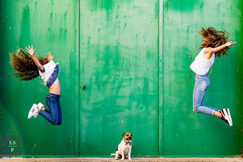 Pyrenees-Orientales girls jump against a green background near their sitting Dog during a lifestyle portrait shoot in Perpignan
