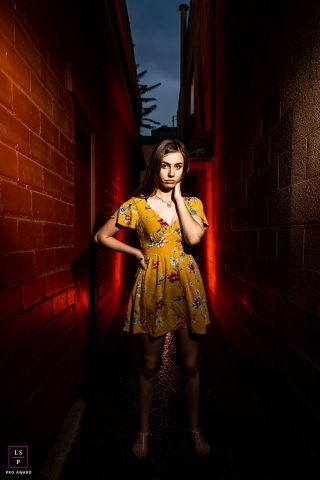 A Colorado High school senior poses in an alley lit with red during a late afternoon lifestyle photo session in Boulder