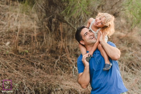 A Madrid Father and daughter have fun together with her on his shoulders on a nature trail in Spain during a lifestyle portrait shoot